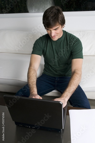 Young man with laptop computer on couch