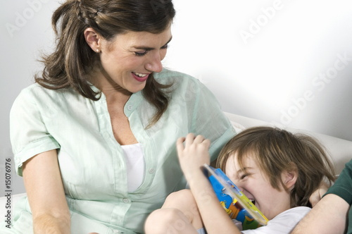 Young woman on couch with boy reading