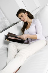 Young woman on couch reading magazine