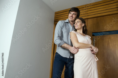 Young couple embracing outside house