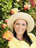 smiling woman in hat staying in the garden poster
