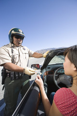 Police officer checking driver's ID
