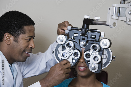 Optometrist examining patient's eyes