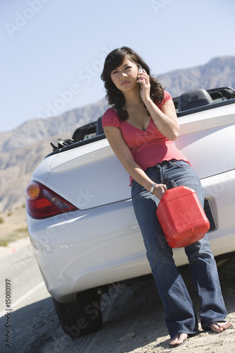 Female driver on mobile with petrol canister at roadside