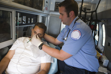 Paramedic tending victim in ambulance