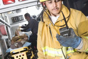 Firefighter using radio, paramedic tending victim