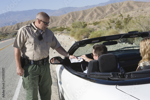 Police officer examines papers of convertible driver