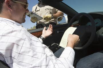 Police man giving man speeding ticket