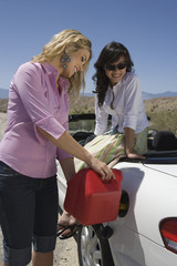 Two young women refuelling car