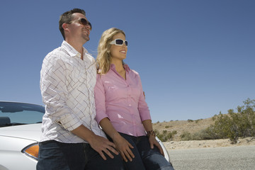 Couple leaning on car in desert