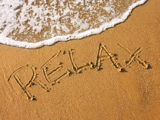 relax written in the sandy beach