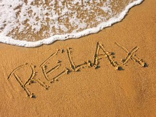 relax written in the sandy beach