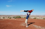 A couple performing a lift in the desert of Moab, UT.