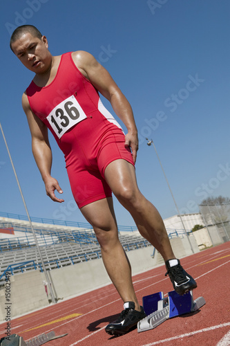 Male sprinter preparing to start