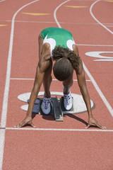 Female athlete in starting block ready to run