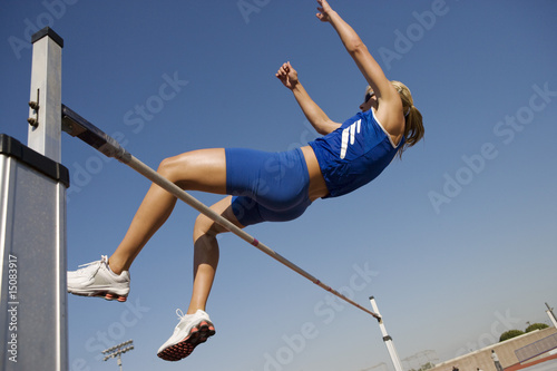 Female athlete high-jumping, low angle view