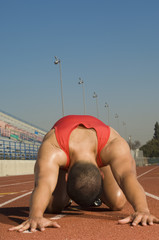 Male athlete stretching on track