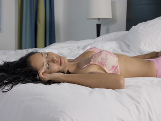 mid-adult woman lying down on bed and sleeping