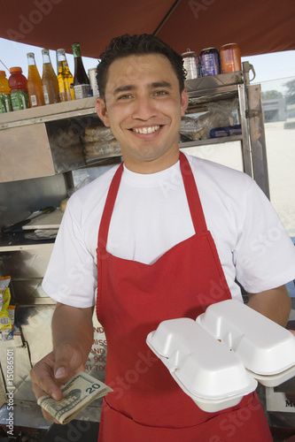 Portrait of male street vendor holding food