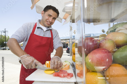 Portrait of male street vendor chopping fruit