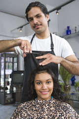 Portrait of barber cutting young womans hair