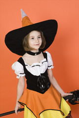 Girl 7-9 wearing witch costume for Halloween, studio shot