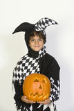 Portrait of boy 7-9 wearing jester costume, with jack-o-lantern