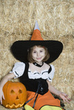 Portrait of girl 7-9 wearing witch costume by hay