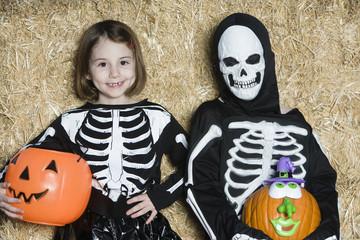 Portrait of girls 7-9 wearing skeleton costumes, with jack-o-lanterns