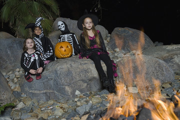Portrait of boys and girls 7-9 wearing Halloween costumes by campfire