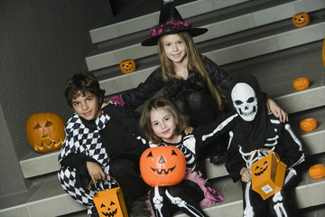 Portrait of boys and girls 7-9 wearing Halloween costumes on steps