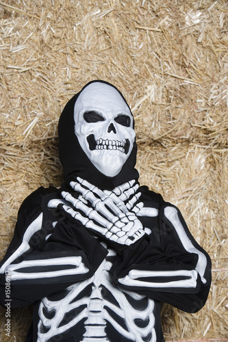 Portrait of child 7-9 wearing skeleton costume by hay