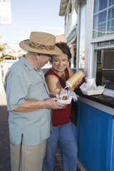 Senior couple buying hot dogs at food stand