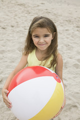 portrait of girl holding beachball on beach  smiling