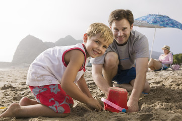 father building sandcastle with son on beach