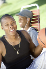 Young Man Holding Basketball, Relaxing with Friend