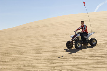 young man on atv on sand dune