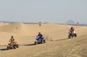 three young men riding atvs on dunes