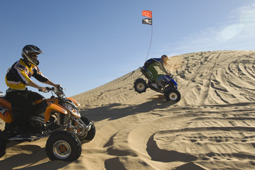 young men riding atvs over sand dunes