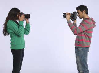 Young woman and young man photographing each other, studio shot