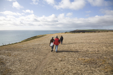Three adults walk along a coastal cliff
