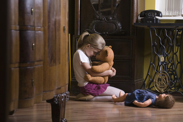 Girl embracing teddy bear on floor in home