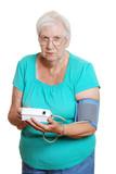 Senior woman unhappy using automatic blood pressure machine poster