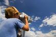 Boy look into metal binocular at beautiful sky
