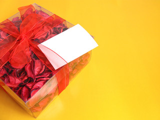 Red Potpourri gift with a white card, on yellow background