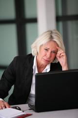 Femme d'affaires senior inquiète devant un ordinateur portable
