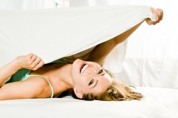 Frau lacht unter einer Bettdecke