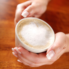 cup of coffee with whipped milk in hands
