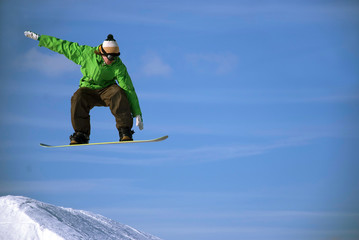 Photo of a snowboarder is jumping against a bright blue sky.