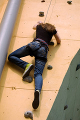 A girl climbing persistently to the top of the wall